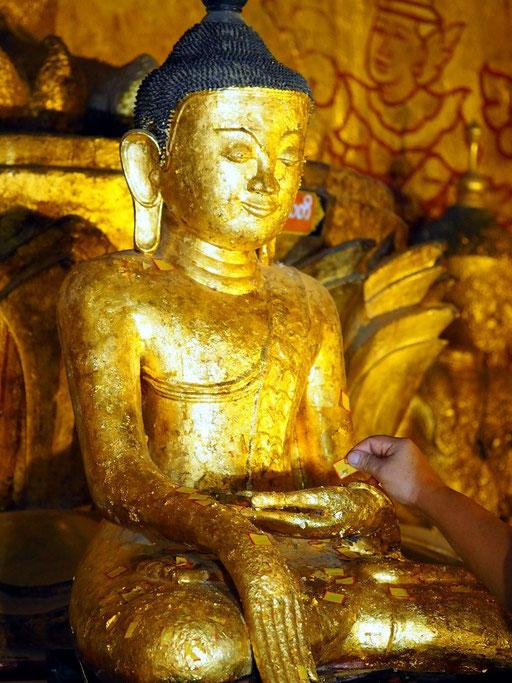 Ritual - Burmesin beklebt Buddhafigur mit Blattgold