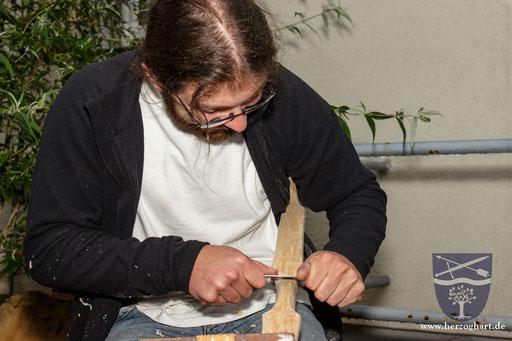 Dustin bearbeitet vorsichtig mit dem Messer die Oberfläche des Bogenrohlings. /Foto: Stephan