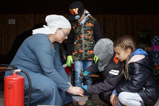 Sonja zeigte den Kindern, wie sie die einzelnen Metallplättchen verformen konnten. /Foto: Stephan
