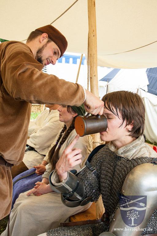 Nach dem schweißtreibenden Kampf braucht Daniel ersteinmal eine Erfrischung. In der Rüstung ist man nicht sehr beweglich, deswegen hilft ihm Stephan. /Foto: Julia