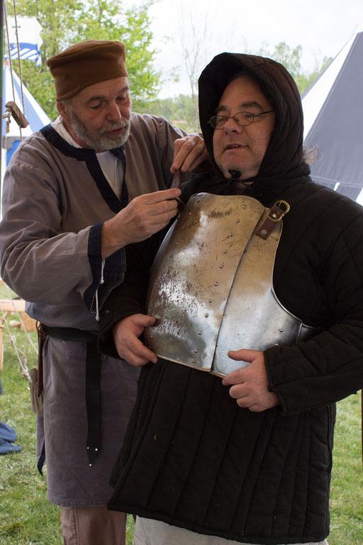 Eine Rüstung kann schwer alleine angezogen werden, daher hilft Ernst Roland, seinen Brustpanzer anzulegen. /Foto: Julia