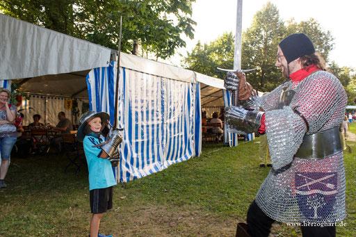 Die jungen Gäste versuchen sich auch gern einmal in Rüstung gegen einen Kämpfer von uns! /Foto: Stephan