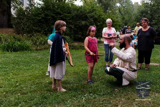 Frederik (rechts) erklärt den Kindern, wie das Kinderarmbrustschießen funktioniert. /Foto: Stephan