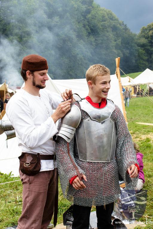 Stephan (links) hilft einem interessierten Jungen in die mittelalterliche Rüstung. /Foto: Julia