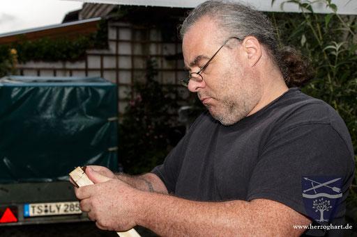 Roland bearbeitet mit dem Messer die Enden des Bogenrohlings. /Foto: Stephan