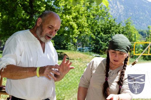 Ernst (links) und Renate (rechts) beratschlagen über die Zubereitung von Brot über dem Lagerfeuer. /Foto: Stephan