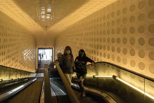 3 Damen, den Unterarm lässig auf den Handlauf gestützt nutzen die Rolltreppe nach oben