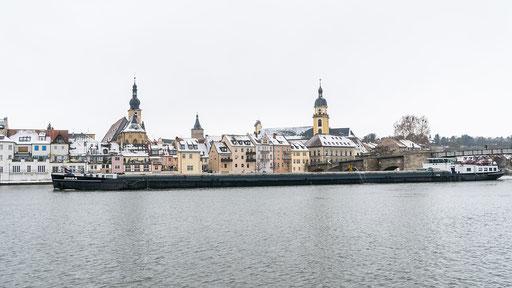 Ein Frachtschiff gleitet flußabwärts an der Stadt vorbei