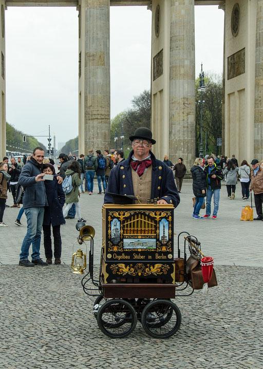 Ein Leierkastenmann spielt vor dem Brandenburger Tor