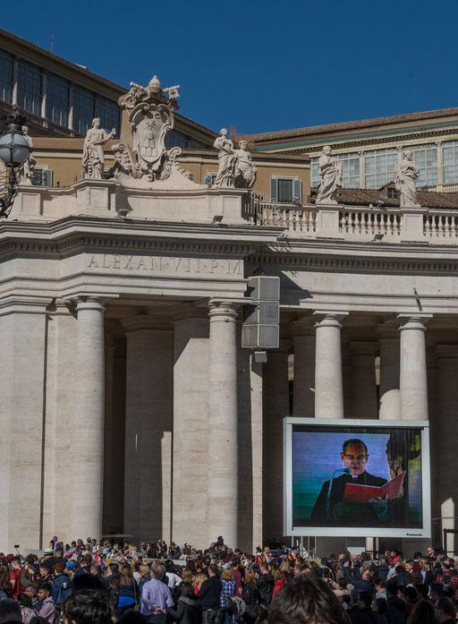 Ein Mitarbeiter des Papstes verliest Grußbotschaften an die gläubigen Pilger