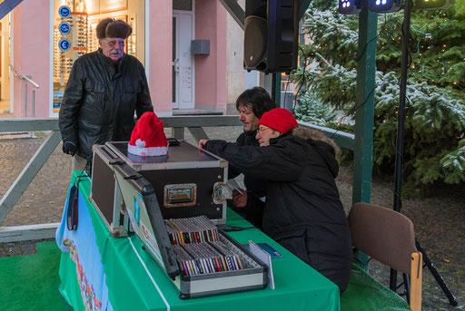 Walter und Achim sind mit musikalischen Dingen beschäftigt,  während Hobbyfotograf Helmut Beer aufmerksam den Marktplatz beobachtet.