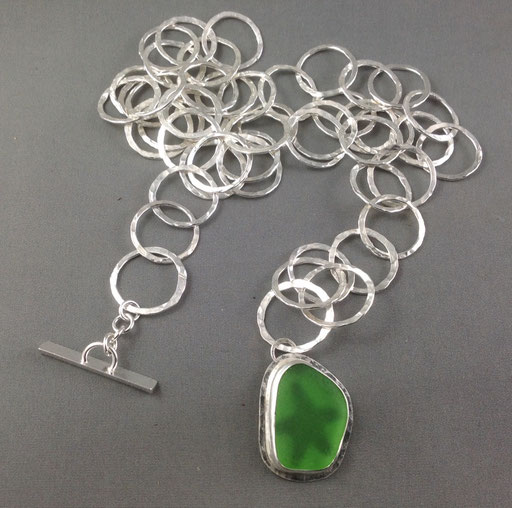 """A long lariat style hammered chain with a bright green sea glass pendant and a starfish """"peekaboo""""."""