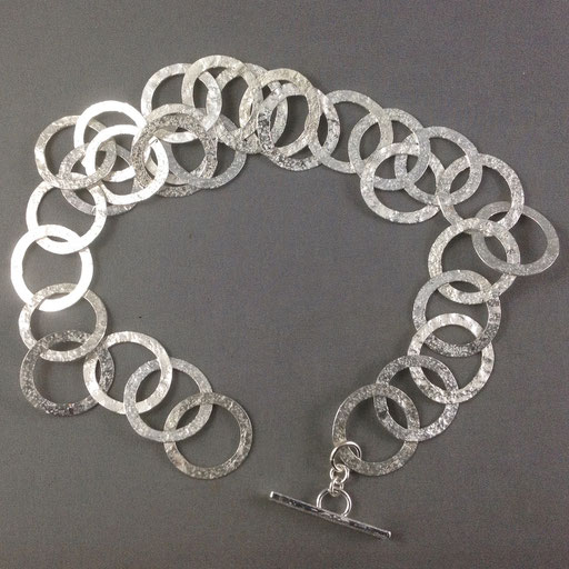 A chain of flattened rings that were textured in a rolling mill with sandpaper for lots of sparkle.