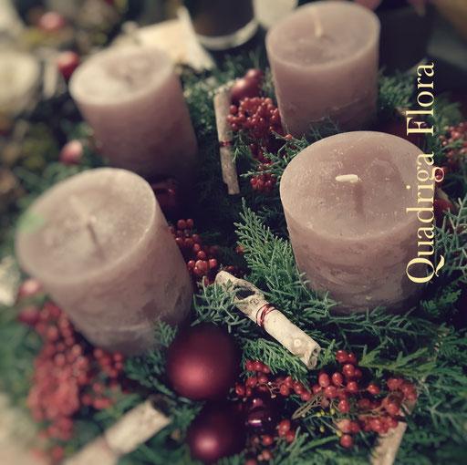 Runder Advents Kranz mit Lila violetten Kerzen und matten Weihnachtskugeln.