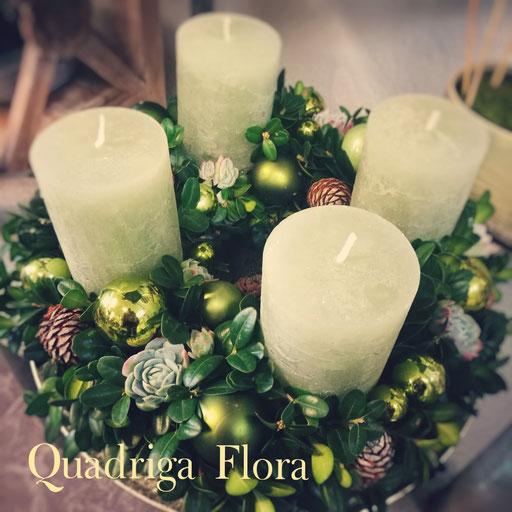 Adventskranz in verschiedenen Grüntönen mit breiten Kerzen in weiss.