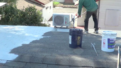 Homeowner rolling the first coat of Ceramic InsulCoat Roof on his Asphalt Shake Roof