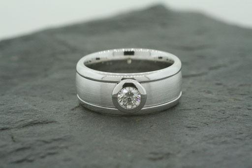 Ring aus Weißgold, außen poliert, mittleres Segment im Bürst-Schliff mit einem Brillanten