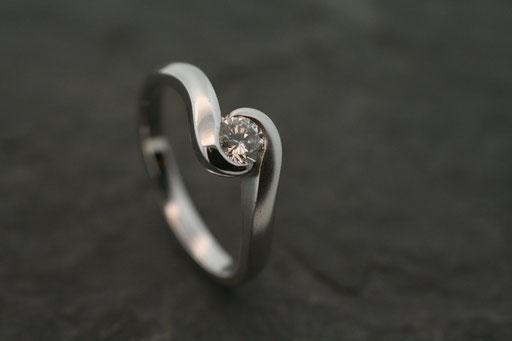 Ring aus Weißgold mit einem Brillanten in geschwungener Zargenfassung