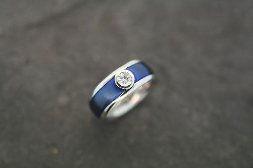 Ring aus Weißgold mit gebläuter Titan-Einlage mit einem Brillanten in Zargenfassung