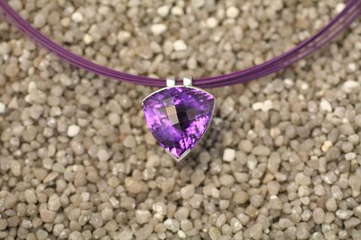 Anhänger mit violettem Amethyst in Zargenfassung an einem Stahlreif in violetter Kunststoffummantelung