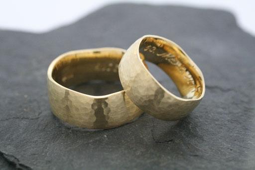 Trauringe / Eheringe aus Gelbgold mit geschwungenem Rand und gehämmerter Oberfläche