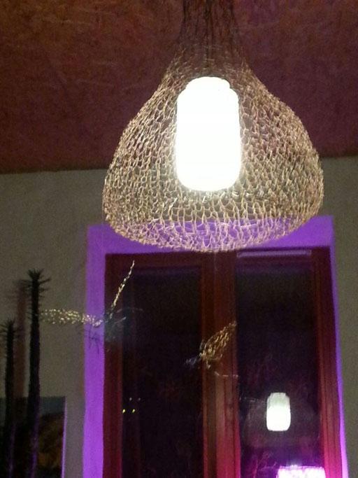 Die neue Deckenlampe, gestrickt aus Eisenfäden - darunter hängen  Engelein
