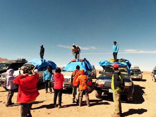 Die Touristen und ihr Gepäck werden an der Grenze von den Bussen in die Expeditions-Fahrzeuge umgeladen