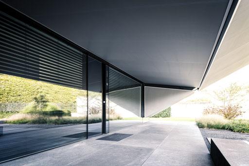 Die Glasfuge mit verglaster Haustür und großformatigen Steinplatten, Foto: Daniel Hartz