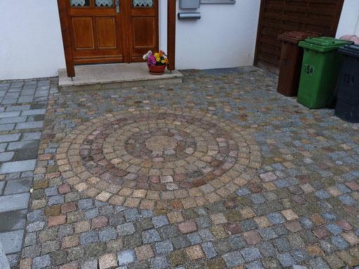 Im Kreis wie auch auch auf der gesamten Pflasterfläche wurden alte Steine eines Klosters verwendet