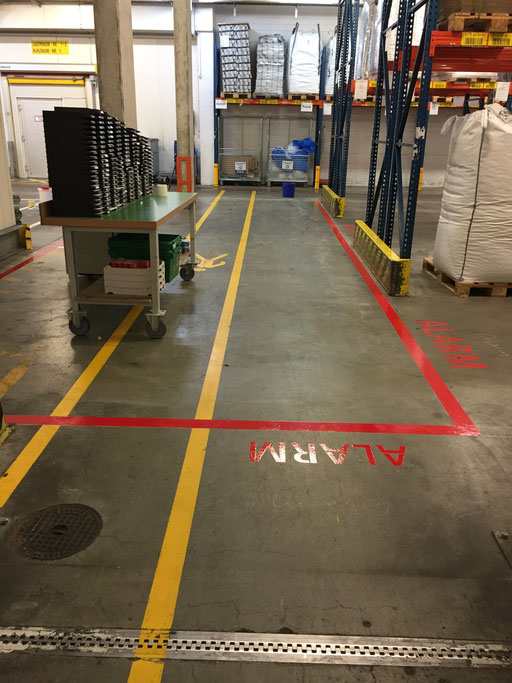 """Markierung von Sicherheitslinien mit Beschriftung """"Alarm"""" in einer Industriehalle"""