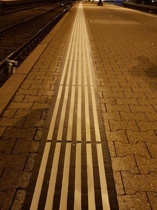 Taktile Führungslinien, für sehbehinderte- und blinde Menschen an einem Bahnhof