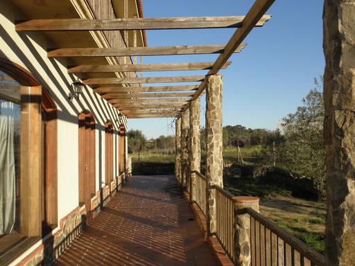 Gran terraza circundando la Casa, esta vista es de la cara Sur, que queda en sombra en verano, bajo la pergola de madera y las plantas de parras.