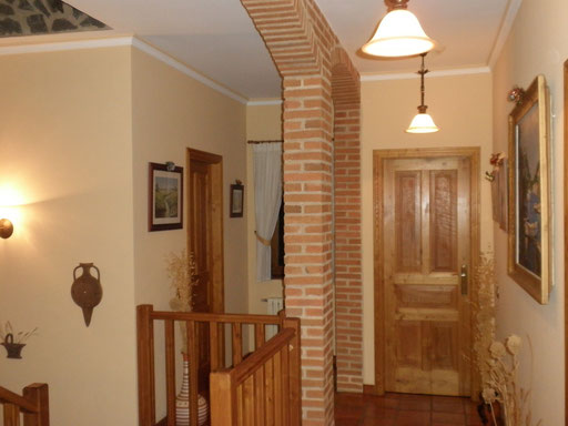 Distribuidor de escalera, pasarela y pasillo en la segunda planta. Los arcos de ladrillo macizo visto dominan el espacio.