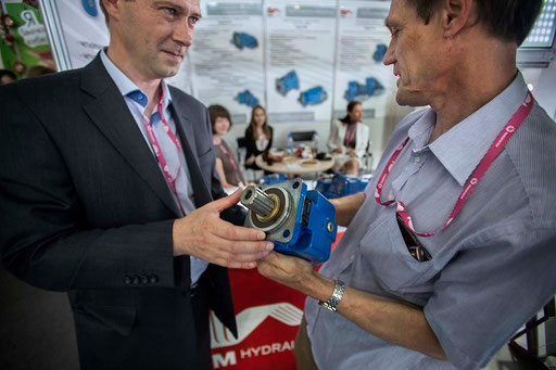 At main Russian International Industries fair 'INNOPROM-2013', Yekaterinburg. Dr. Andrey Kaletin (on right), head of International Programs Department of UCEE, holds in hands a turbine with Michael Kislyak, head of Marketing Department of PSM-Hydraulics.