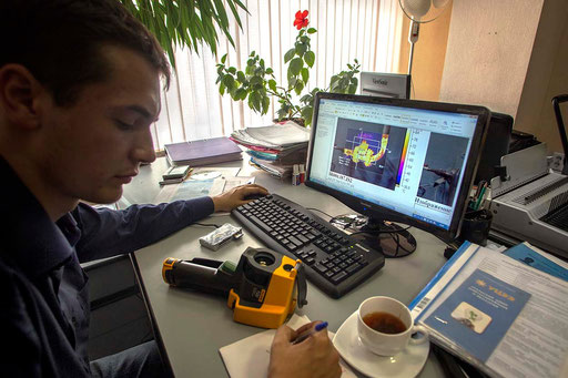 UCEE Energy Efficiency Department specialist, Anton Gilev, developing a heat scheme, with images of a hydraulic implant of a home just downloaded on pc from memory card of the 'Thermograms Instrument' (on the desk), measuring heating by infrared lights.