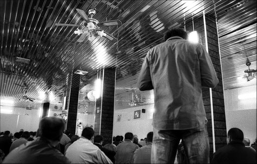 "In the main underground room of the mosque, during ""Jumu'ah"", friday in Arabic and main pray day of Muslim week. Before the pray, the Imam is speaking the sermon to the faithfuls."