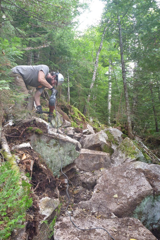 Jed drills to split a large boulder that could not be moved out of the trail tread