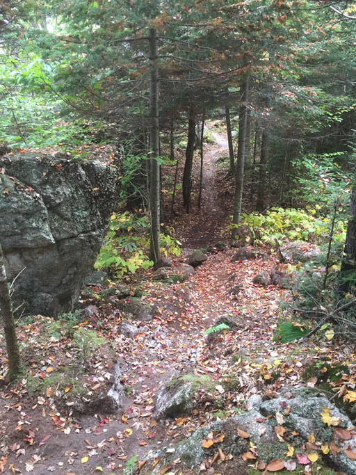 The trail meanders past large boulders