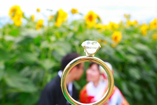 ひわまり畑で遠近法で指輪の中に入る新郎新婦様