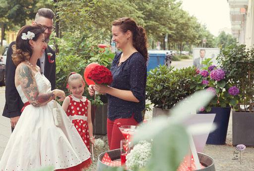 Hochzeitsplanerin begrüßt das Brautpaar u. nimmt der Braut den Brautstrauß ab