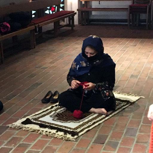 Frau mit Kopftuch sitzt im Schneidersitz auf dem Teppich