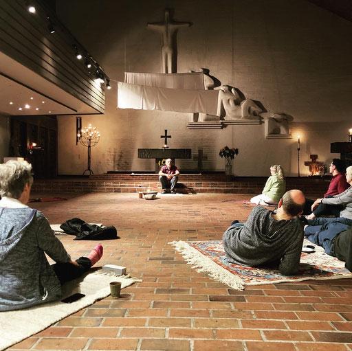 Menschen in der Jubikatekirche sitzen alle aufTeppichen