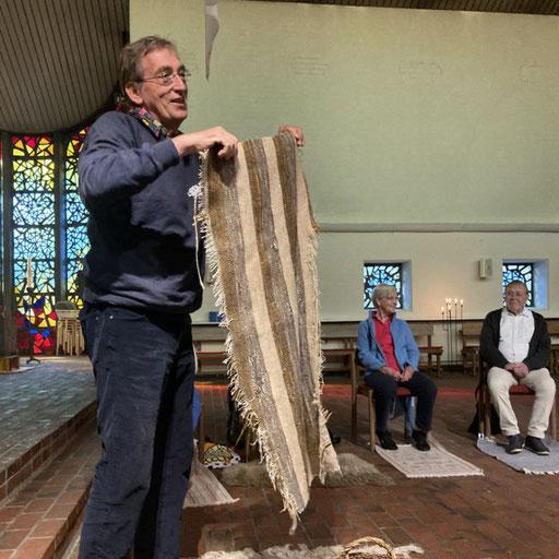 Pastor Bothe präsentiert Teppich in der Kirche