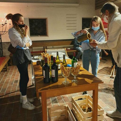 Tisch mit Wein und Salzgebäck und Menschen drumherum