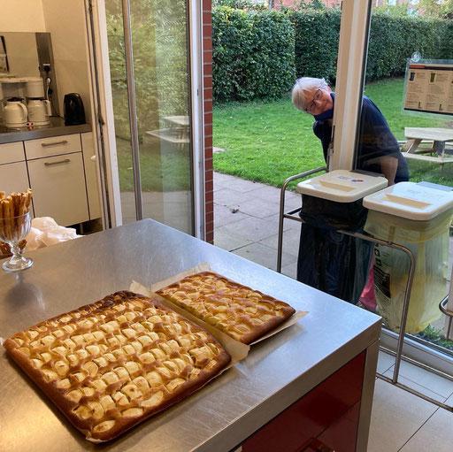 Frau guckt durch Fenster in die Küche, dort steht Kuchen
