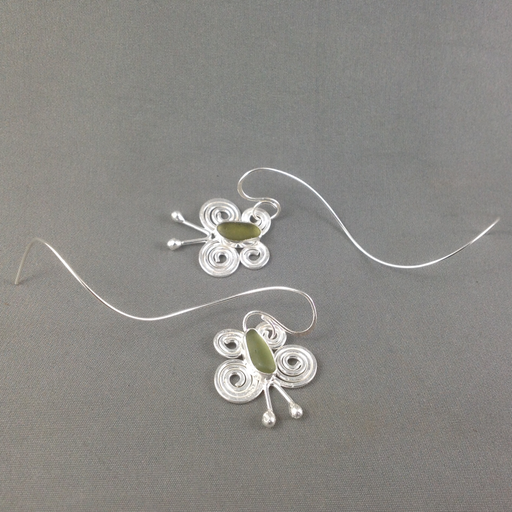 Flutter by with these filigree sea glass butterflies on whimsical swirly earwires.