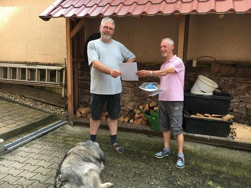 Friedbert Kern überreicht eine Urkunde und Plakette für ein schwalbenfreundliches Haus (E. Kübler, Juli 2021)