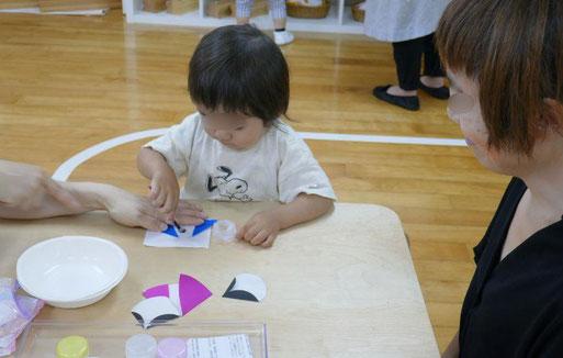 未就園児・親子で学ぶコースの生徒がモンテッソーリの個別活動でお母様といっしょに七夕の飾りとして折り紙を使って、おり姫とひこ星を製作しています。