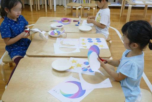 モンテッソーリの個別活動で、年中児と年長児が、七夕飾りの製作活動に取り組みました。難しい形を切って貼り、星のストリングスデコレーションを製作しているところです。