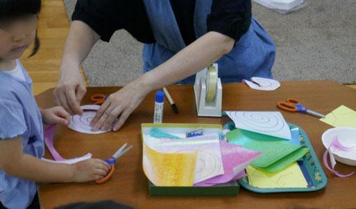 モンテッソーリの個別活動で、年少児が七夕の飾りを製作。星と渦巻きをはさみで切って、流れ星を製作しました。